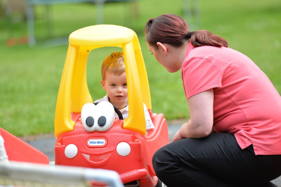 A mother watching her child play in a toy car.