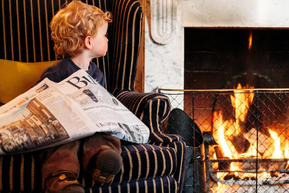 At a luxury family hotel, a boy sits by the fire with a newspaper