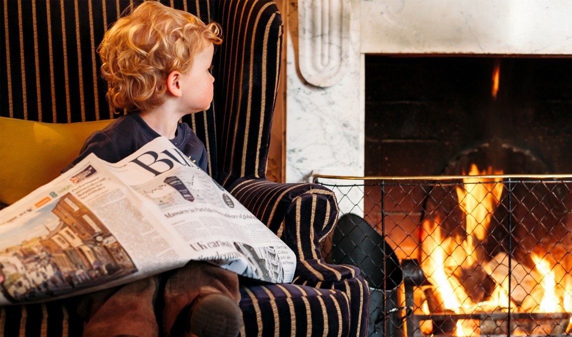 A boy sits by the fire at one of the luxury family hotels