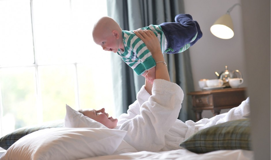 A mum lifts her child into the air, smiling.