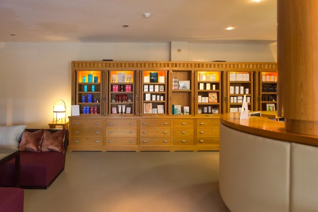 Beauty products lined on wooden cabinets in the New Park Manor spa reception.