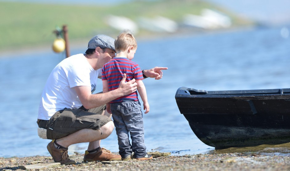 A father and son stand on the coast near a luxury family hotel