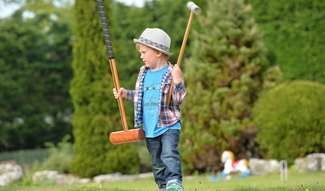 Child playing croquet in the grounds of New Park Manor